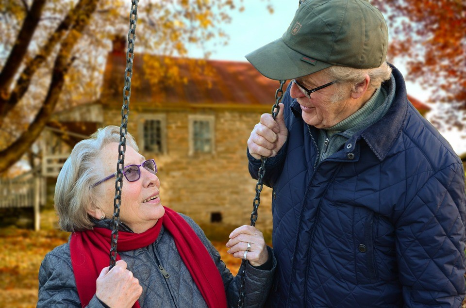 Ein älteres Paar, das sich anschaut, während die Frau auf einer Schaukel sitzt